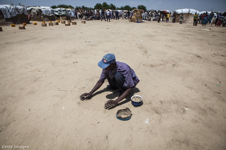 Ételosztás után széthullott babszemeket gyűjt egy férfi Mongunóban, 2016. szeptemberében.
