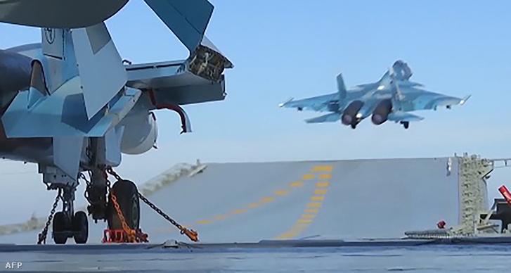 Képkocka az orosz védelmi minisztérium nyilvános videójából, amin a Földközi-tengeren állomásozó Kuznyecov repülőgép-hordozó látható. A minisztérium szerint a szíriai orosz légicsapásokban a repülőgép-hordozó is szerepet kapott.