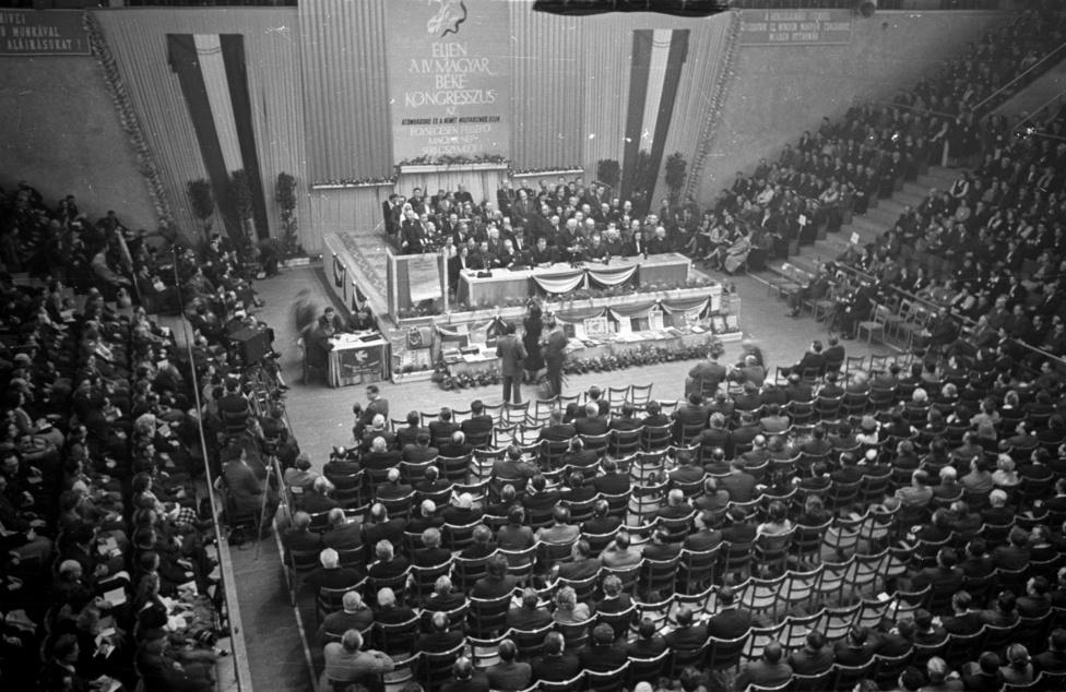"""A IV. Magyar Békekongresszus 1955 februárjában az akkori Nemzeti Sportcsarnokban (ma Gerevich Aladár Nemzeti Sportcsarnok). Az 1950-től évente megrendezett találkozókon együtt dobbant nagyot és hangosat a sok, """"világbékéért harcoló szív:"""" politikusok, írók, művészek, főpapok, parasztasszonyok, sportolók, élmunkások szíve. A fotón az elnöki emelvényen Kisfaludi Stróbl Zsigmond szobrászművész nyitja meg a kongresszus tanácskozását. """"Az atomháború és a német militarizmus ellen egységesen fellépő magyar nép seregszemléjét"""" nem tarthatták meg """"békepapok"""" nélkül. A belső széthúzóerőként létrehozott, állami sugalmazásra 1950-ben megalakult """"békepapság"""" és irányírója, a Katolikus Papok Országos Békebizottsága visszautasította azt a vatikáni és """"nyugati"""" politikát, amely ellenséges a Népköztársasággal és támogatta az egyháznak az állammal való megegyezését. Szerintük """"ez a megállapodás milliók vágyát teljesítette és határkő a magyar egyháztörténelemben. A katolikus egyház és a papság odaáll a magyar dolgozó milliók mellé, mert ott a helye."""" A rájuk ragadt elnevezést büszkén viselték: """"az, hogy bennünket egyesek gúnyosan 'békepapnak' neveznek, csak megtiszteltetés és dicsőség"""" – mondta az 1950-es alakuláskor Balogh páter a Szabad Népnek."""