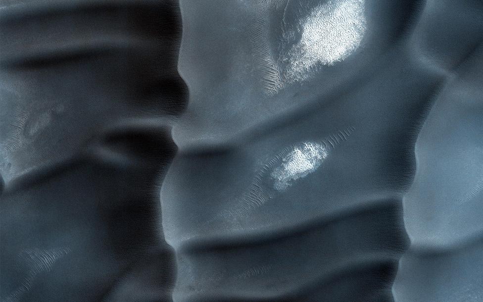 Július 15. Szélfútta homokdűnék a Mars északi sarkához közel, az Olympia Undae nevű térségben. A dűnék érdekességét az adja, hogy nem a megszokott kőzetből, bazaltporból vannak, hanem gipszből. A képet a Mars Reconnaissance Orbiter (MRO) műhold készítette.