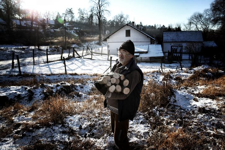 Fát cipel egy férfi a nógrád megyei Karancslapujtőn, az év leghidegebb napján