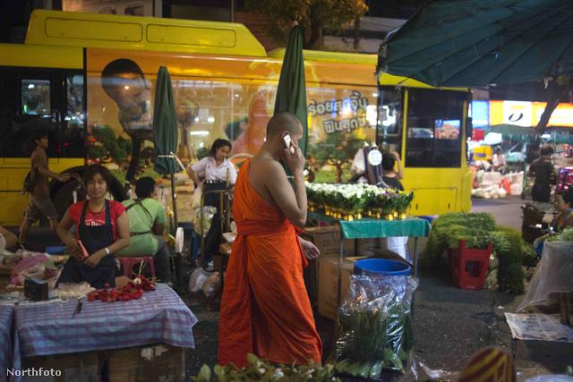 Szuper fotó az ájszakai Bangkokból mobiltelefonáló szerzetessel