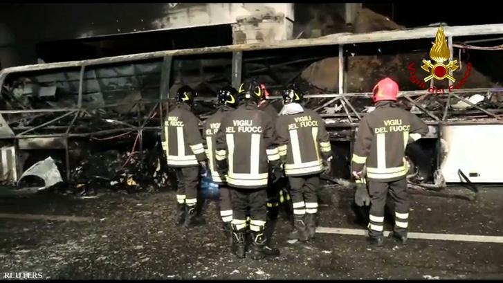 Tűzoltók dolgoznak a kiégett busz roncsainál