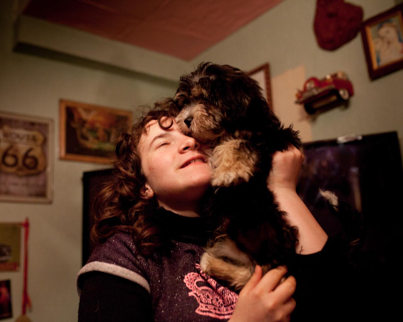 A család öt kutyájából a képen Kapitányt (Capitaine) szeretgeti átszellemülten Ilona. A háttérben a falakon megfigyelhetők a mindent elárasztó, ocsmány amerikás falidíszek.