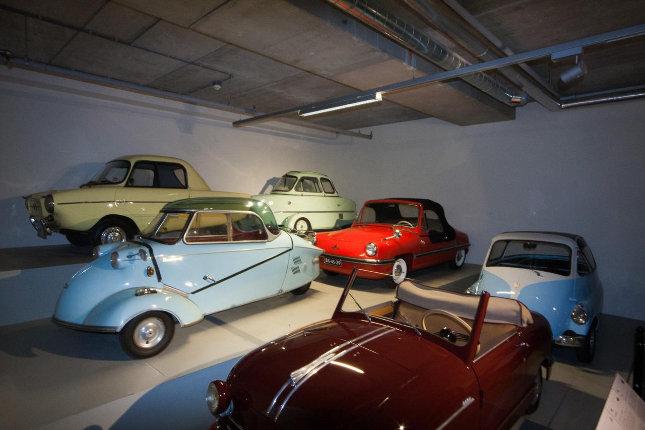 A másik minimálautó-terem egy sarka: a felső polcon Frisky Family Three (1960), Inter Cabin Scooter (1955), alatta a Messerschmitt Kabinenroller KR200 (1959), Spatz (1956), majd legalul a már említett Rovin, mögötte egy Isetta, de nem a BMW-féle, hanem még az eredeti, olasz ISO-gyártmány.