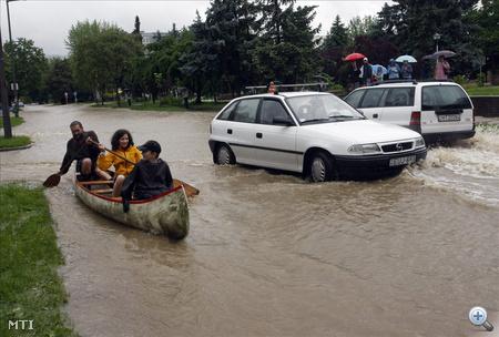 Emberek csónakkal közlekednek Miskolcon a Kilián városrészben, miután az esőzések következtében megáradt és kiöntött a Szinva patak.