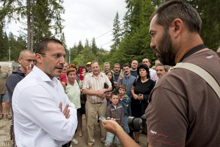 Lénárd András, a Xindex Eco kivitelezőcég tulajdonosa (b) egy újságírónak válaszol a Hargita megyei Homoródfürdőn, ahol helyiek gyűltek össze tiltakozni a vízerőmű megépítése ellen 2013. július 23-án
