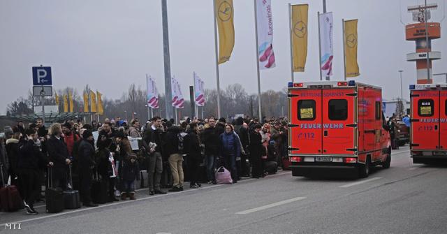 Utasok várakoznak az utcán, mellettük a helyi tűzoltók