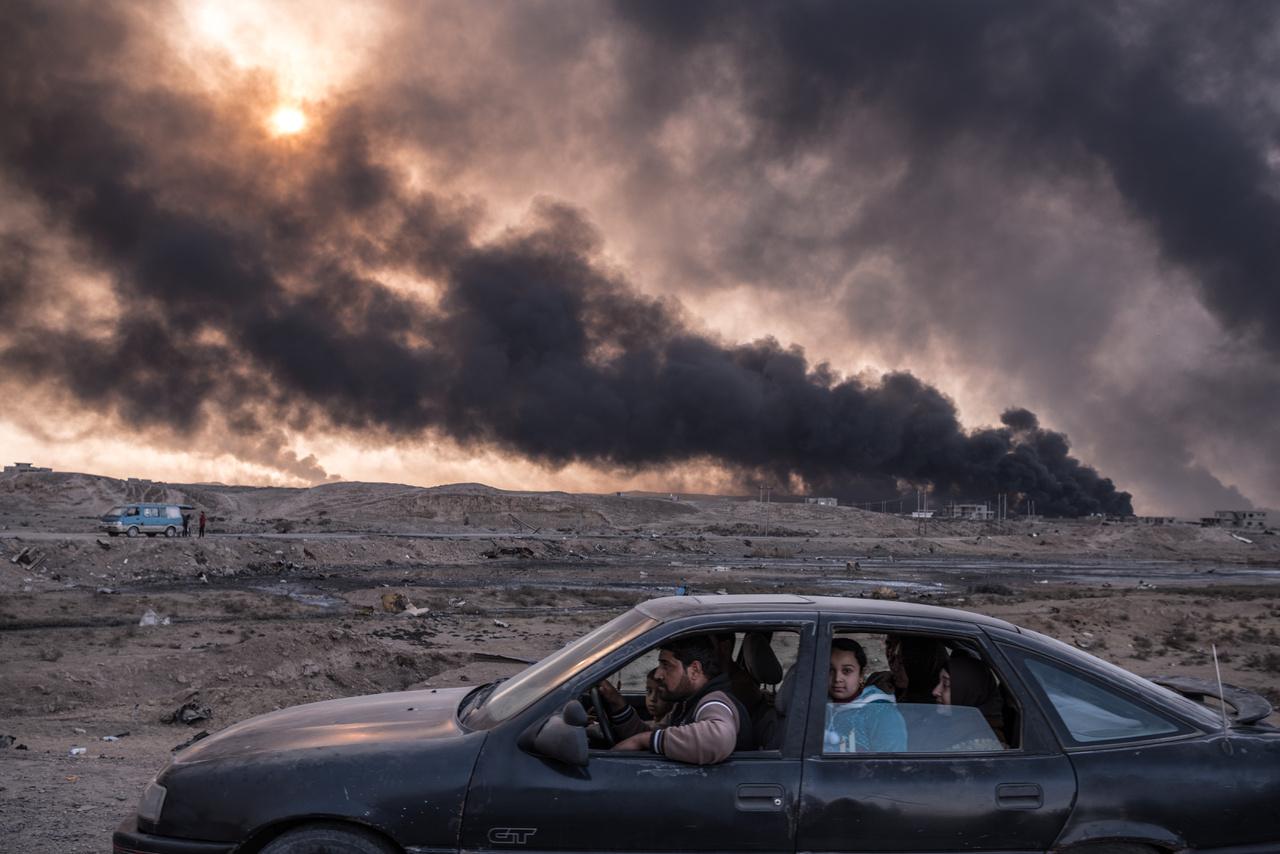 Kiemelt hírek (sorozat) III. helyMoszul ostroma elől menekülő iraki civilek a várost elkerülő autóúton. A háttérben a füst és a lángok a város körül felgyújtott gyárakból és olajmezőkből szállnak fel.