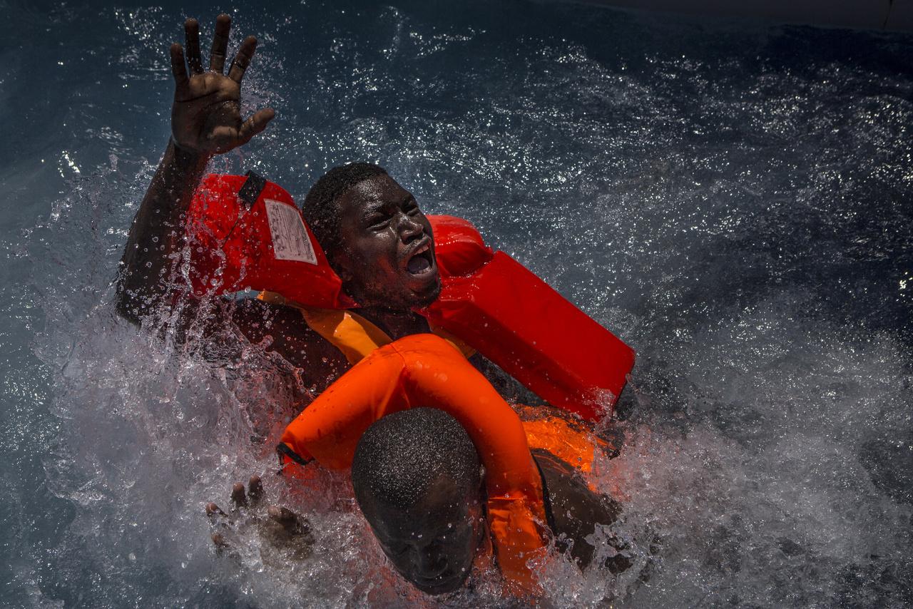 Két menekült próbál a víz felszínén maradni, amikor az őket szállító csónak felborult a Földközi-tengeren.
