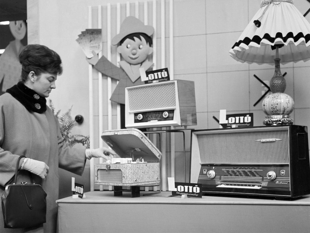 """Nő szalagos magnetofonnal a Rákóczi úti Lottó Áruházban 1963-banAz 1950-1960-as években az ország legmodernebb áruházának kikiáltott szocialista pláza a lottó-tárgynyeremények állandó bemutatója és beváltóhelye volt. És többmillió magyar nem tévedhet: """"A lottózók a Lottó Áruházban vásárolnak!"""" - szólt a reklám."""
