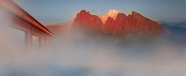 A Dolomitok az Adler Mountain Lodge kültéri medencéjének párájában