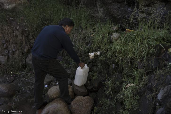 Vizet vesz egy férfi egy természetes kútból La Paz külvárosában.