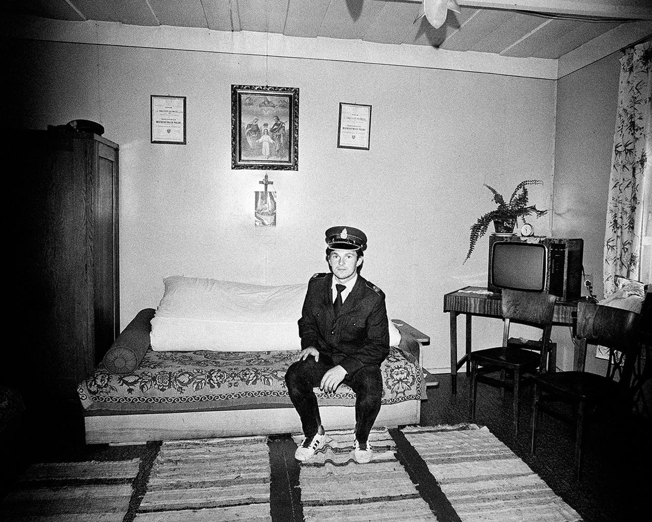 Ifjú rendőr a hagyományos paraszti tiszta szoba némely funkcióját még őrző helyiségben, a szent családot, mint Krisztust a latrok, jobbról-balról minisztériumi oklevelek veszik körbe.