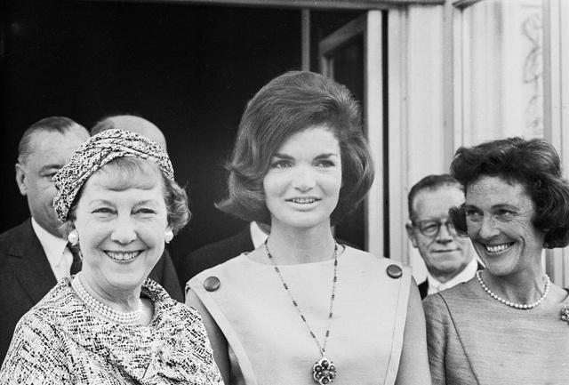 Balra Mrs. Dwight D. Eisenhower, a közvélemény által Mamie-nek becézett leköszönő First Lady, mellett utódja, Jacqueline Kennedy. Eisenhower felesége nem örült, hogy költöznie kell. Mikor körbevezette Jackie-t a Fehér Házban, órákig sétáltatta a két héttel korábban császármetszésen átesett nőt, pedig volt a házban kerekes szék. Később azzal védekezett, hogy Jackie nem ajánlotta fel, mert kérdezte.