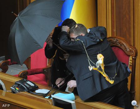 Volodimir Litkin házelnököt esernyővel kellett védeni a verekedés hevében felé dobott tojásoktól.