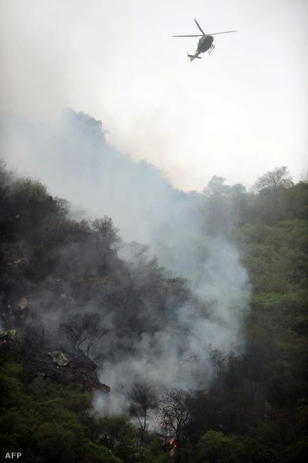 A gép füstölgő roncsai a hegyoldalban