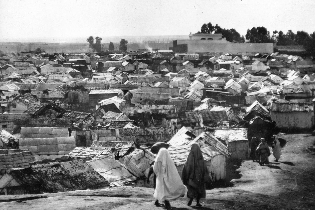 Casablanca nyomornegyede (Bidonville), 1936A névtelen fotós Casablancában is elhagyta az elegáns, koloniális belvárost és az előkelő villanegyedeket, hogy megnézze magának az ezer és ezer hulladék-kunyhóból álló bádogvárost. A szemétből épült hatalmas telepet a harmincas években főleg a nagyvárosban munkát kereső berberek lakták.