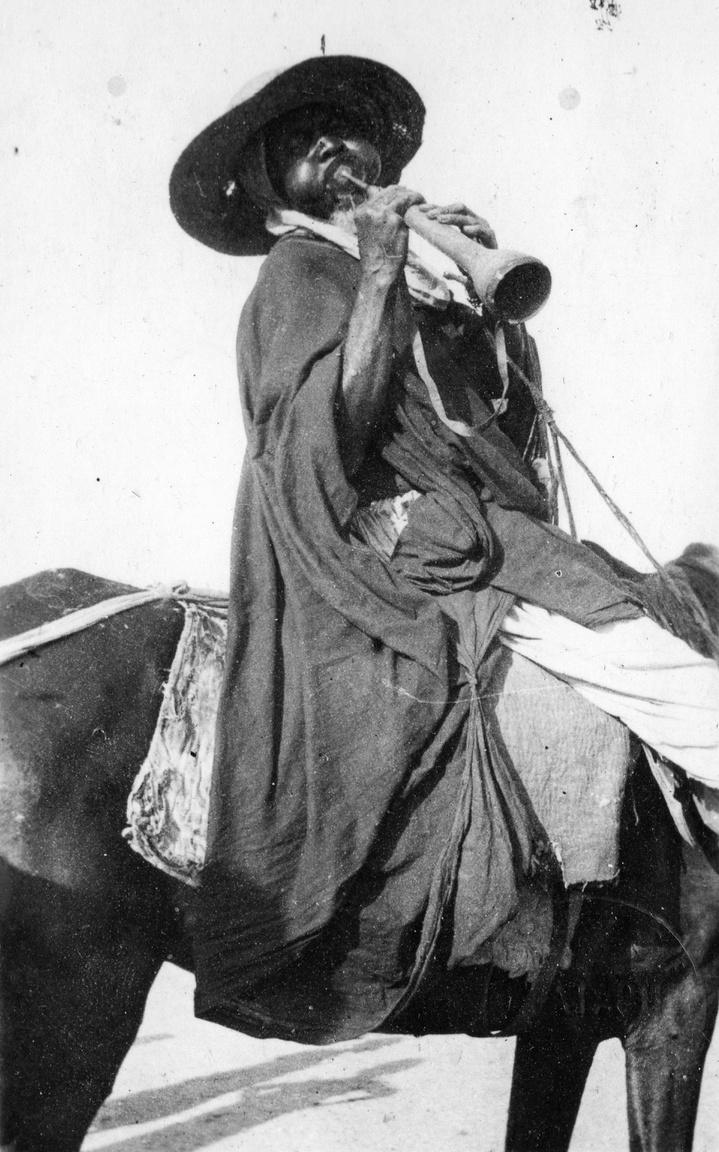 """Afrikai bennszülött az 1930-as évekbőlA rejtélyes albumból nem derül ki pontosan, Afrika melyik részén készült a fotó és ki van rajta. Lehetett éppen az utazók helyi kalauza is. Marokkóban például nem volt ritka a kifogástalan angolsággal beszélő és igazi gentleman berber sivatagi vezető. P. Howard megemlékezett egy különös életútról is: egyikük """"a philadelphiai hangversenyzenekarnál működött évekig, és szerelmi csalódása miatt tért ismét vissza a sivataghoz."""""""