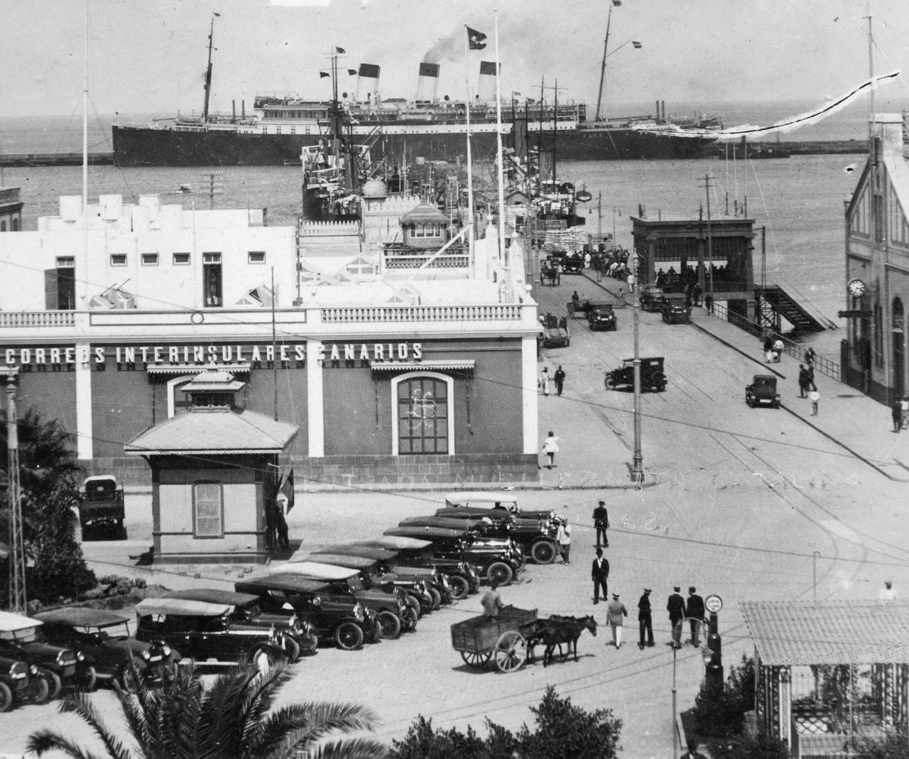 """Las Palmas (Kanári-szigetek), Szent Katalin-móló 1935-benA fotós """"kikötők és dokkok a világ körül""""-sorozatának egy darabja. A kikötői életet Rejtő is több helyen megírta. Apja szerint Algírban ő maga is pakolt ládákat és gyűjtött élményeket kikötői kocsmákban faragatlan asztalok és ugyanilyen vendégek között.A mi névtelen emberünk ugyan nem futott össze sem Vanek úrral, sem Fülig Jimmyvel, de egy hozzájuk hasonló rejtői figurával igen. És neki még a nevét is ismerjük az albumból! Ez az Uhrin Jóska nevű fiú érettségi után színészettel próbálkozott Pesten, de a kaland jobban vonzotta, mint valami kis protekciós állami hivatal. Amikor az ismeretlen nevű fotóssal találkozott itt a Kanári-szigeteken, térképezésből élt és selyemöltönyben járt, derekán cserkészövvel (""""a csatja, ott, ahol a 'Légy résen!' meg a liliom van, jó nagy és kemény vas. Lehet vele alkalomadtán verekedni, s éppen a hasamon van a csat, ami jól jöhet esetleg."""")."""