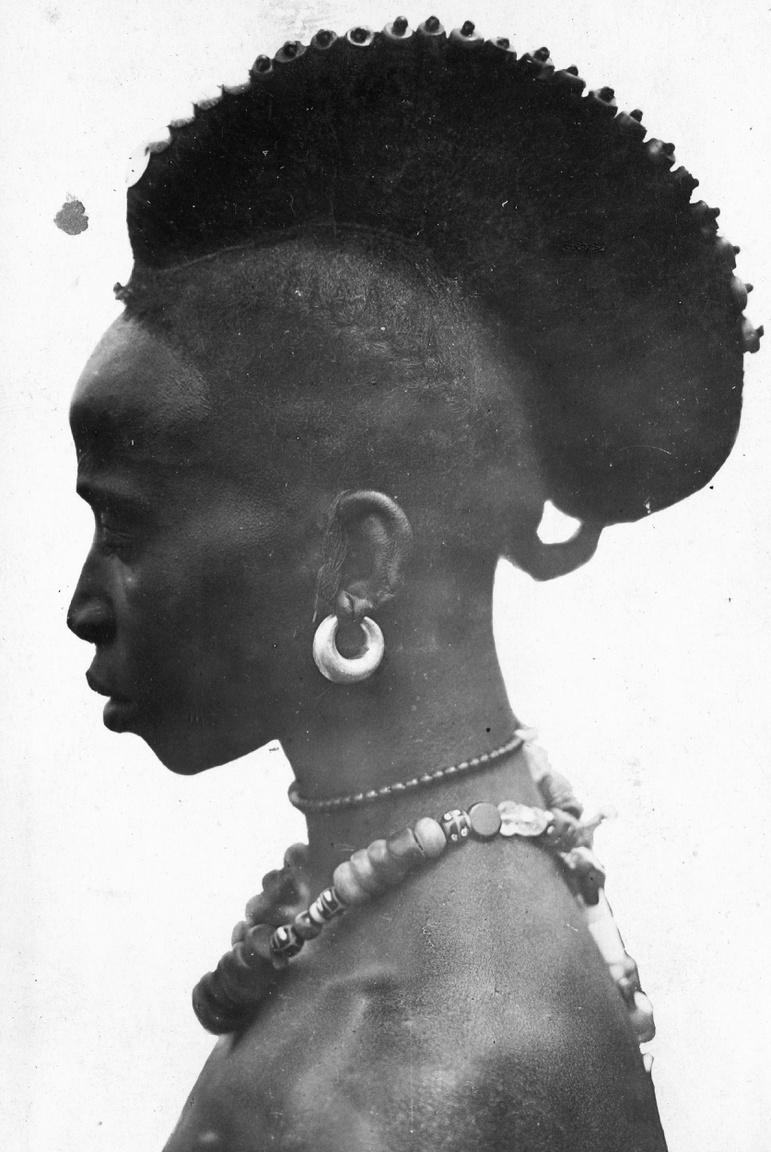 """Afrikai bennszülött portréja a gyarmati időkbőlA névtelen fotós eljutott Afrika európaiak által ebben az időben kevéssé látogatott részeire is. A közvélemény többsége a bennszülötteket barbároknak, legjobb esetben egzotikumnak tekintette ekkoriban. A franciák például 1931-ben gyarmati kiállítást rendeztek (a névtelen fotós is ott volt), hogy bemutassák azt """"a kultúrmunkát, amit a gyarmatosító országok Afrikában, Ázsiában és Ausztráliában véghezvittek""""."""
