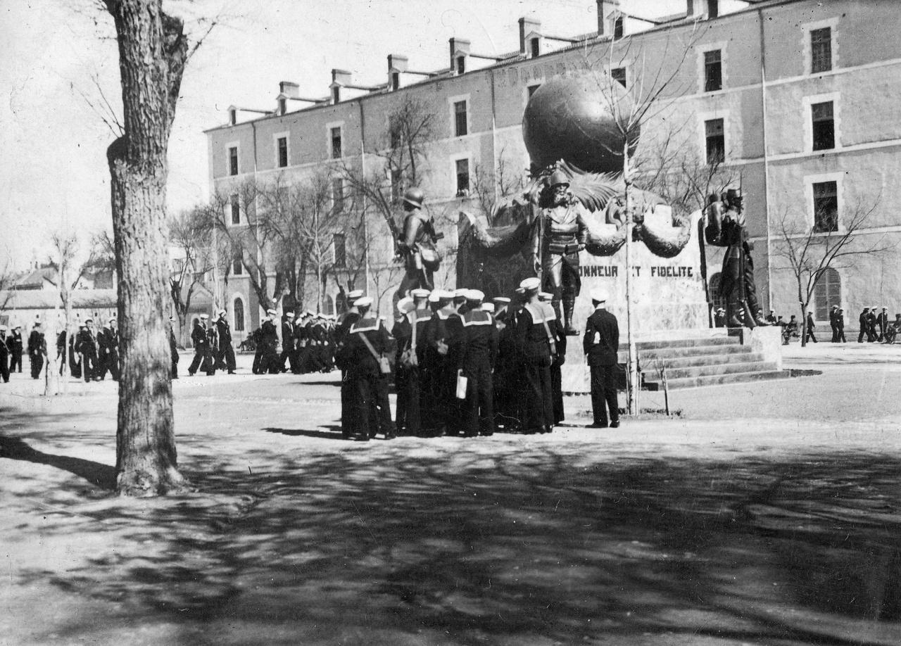 """Algéria, Sidi Bel Abbes. Matrózok az elesett légiósok emlékműve előtt 1935-benSidi Bel Abbes a Francia Idegenlégió katonáinak gyűjtőhelye volt: a """"piszok bleu""""-k, vagyis az újoncok szállítmánya hetente kétszer érkezett Marseille-ből. Bár Gorcsev Ivánt a szerelem sodorta a légióba, a legtöbben a törvény keze vagy a gazdasági válság elől rukkoltak be. Az 1930-as években a lapok rendszeresen cikkeztek a magyar légionisták sorsáról. Az Est szerint 1931-ben összesen 350-400 magyar harcolt az idegenlégióban. Kemény volt az élet, Verdier őrmester csak ironizált A tizennégykarátos autóban, amikor """"elaggott, vidéki levélkézbesítők, lóápolók és reumás nyugdíjasok kényelmes otthonának"""" titulálta, ahol """"teljesen hülyék számára kedvezmény, különleges elbánás, altiszti rangban sürgölődő szárazdajkák"""" tartoznak még az alapellátáshoz."""