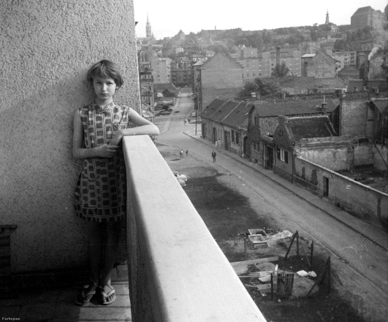 Két világ határán 1966-ban: egy modern épület lodzsáján támaszkodó lányka a Horváth utcában, a másik oldalon még a régi Buda emlékei földszintes házakkal. Ma már irodaházak vannak a helyükön.