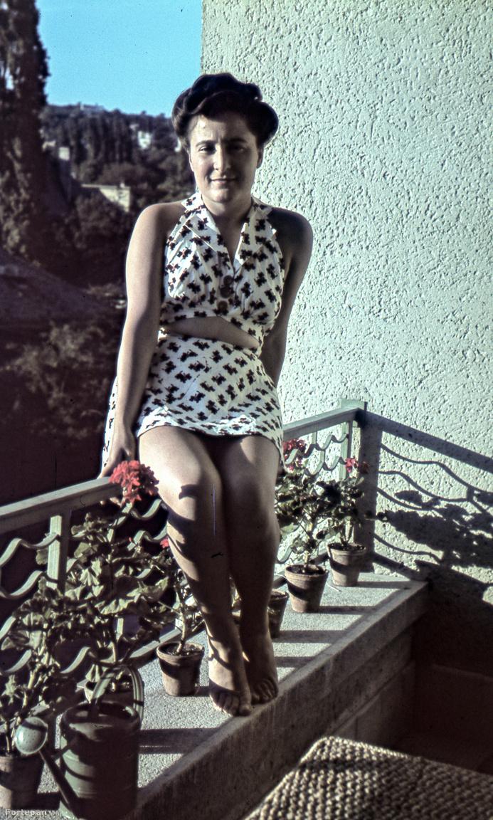 A lodzsa viszont nem lóg ki, belesimul a ház homlokzatába: oldalról falak határolják és felülről is födém zárja le. Ha úgy tetszik az erkély kifelé, a lodzsa befelé alakít ki egy kis nyitott teret. Ezen a színes fotón, ami a budai Torockó utcában készült, nem is tudom, mi a merészebb. Ahogy a nő egyensúlyoz a korláton, vagy a hasvillantós ruhája 1942-ben.