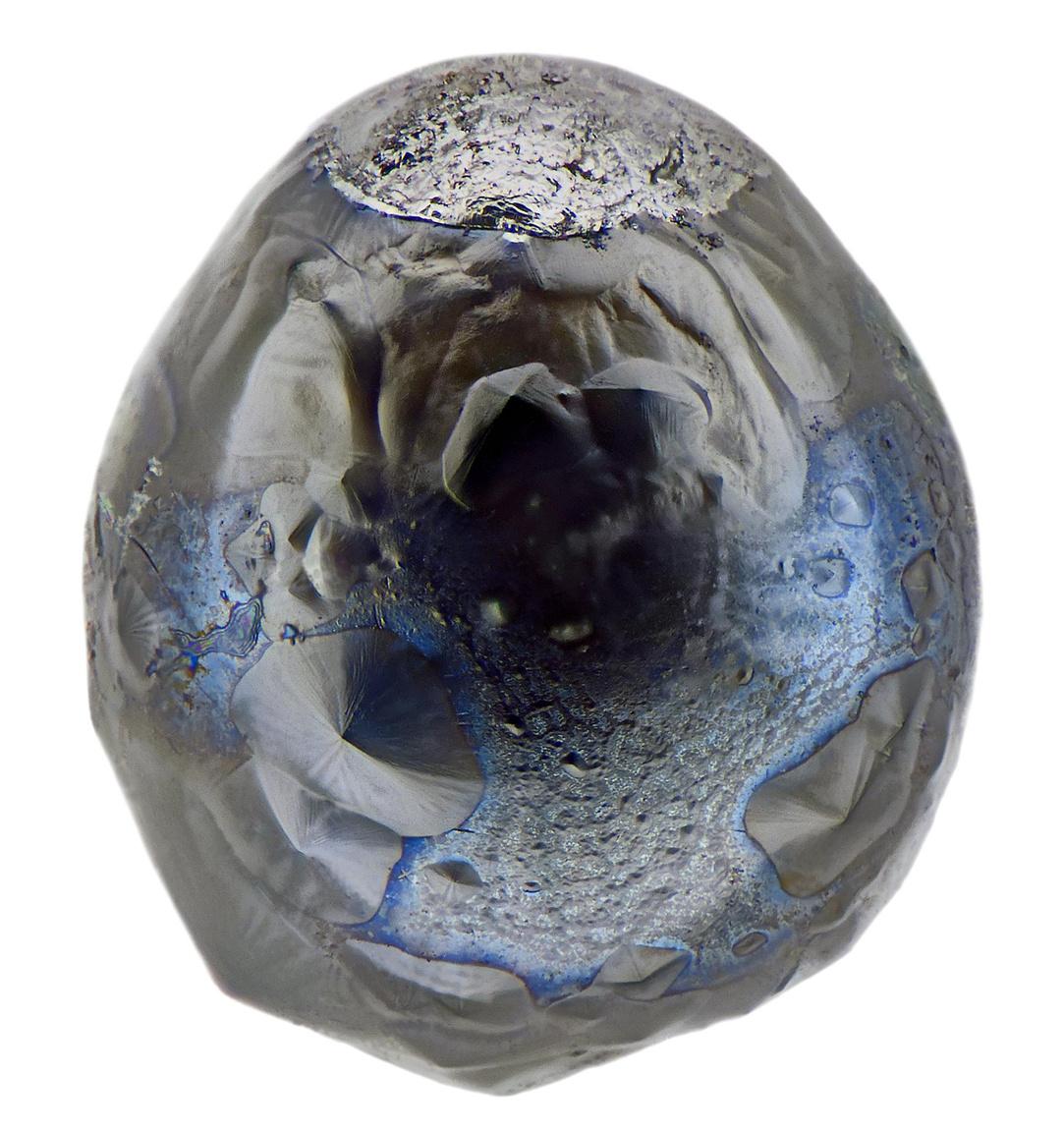 Ez a kb 0,3 mm-es mikrometeorit okoz némi fejtörést az elemzőknek. Annyi biztos, hogy nikkel-vas magja kitüremkedett a légkörben lassulva, de a kékes színű, üvegszerű olvadékra nincs biztos magyarázat.
