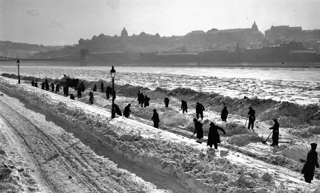 A pesti alsó rakpart a Zoltán utca torkolatánál, háttérben a Lánchíd és a budai Vár, 1942                         Téli napsütés, zajló Duna, kilátástalan harc az óriási hóval. Bár Magyarország 1941 nyarán belépett a háborúba, ebből akkor még keveset lehetett érezni Budapesten.
