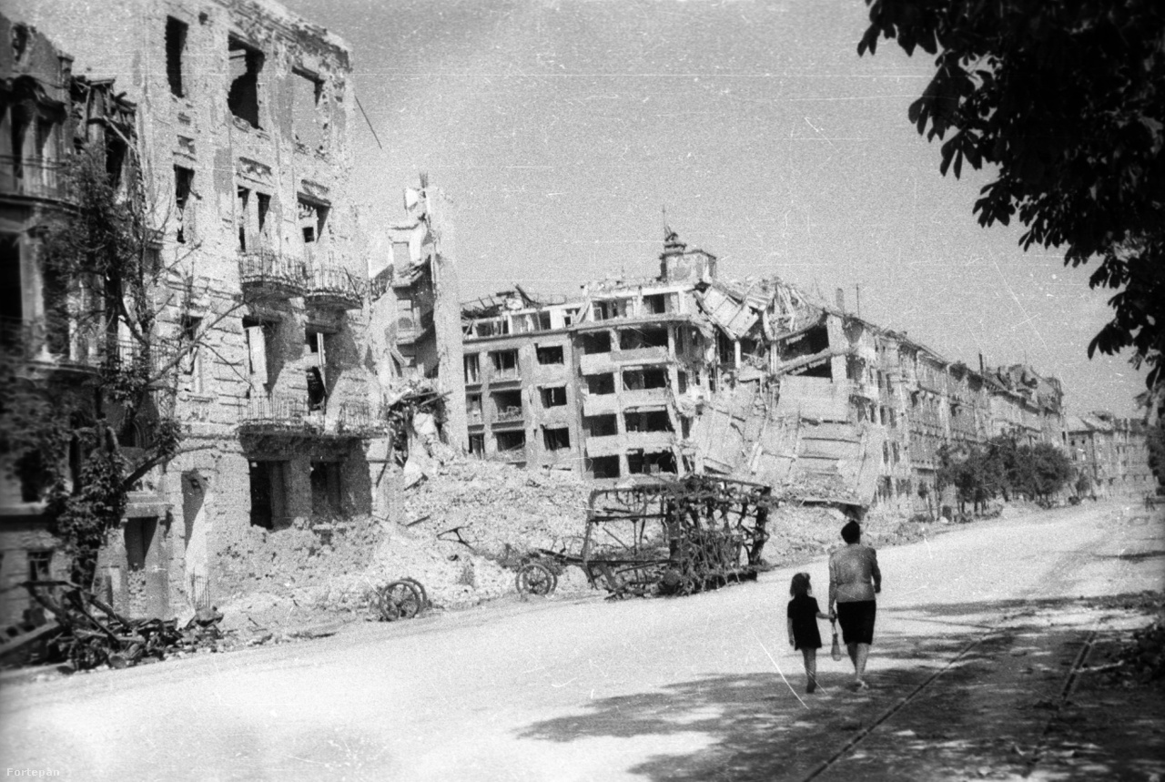 """A Margit (ma Bem) rakpart a Pálffy (ma Bem) tér felé nézve, a Vitéz utca torkolatánál, 1945                         Pár hónappal a háború vége után így festett egész Budapest. A lármásan csengető villamosok, a historizáló és modern bérházak, arisztokrata városi paloták a Margit rakpartról is eltűntek a háborús süllyesztőben. Emlékké szépültek, ahogy Andrássy Katinka esetében is. A későbbi vörös grófnő előbb a Margit rakpart 9.-ben, majd a ma is álló 6-7.-ben élt egészen a házasságkötéséig. Idős korában nosztalgiával emlegette a kötelező és unalmas rakparti sétákat a nevelőnőkkel, """"szélben és viharban, hóban és esőben"""" is. 1914 nyarán az első emeleti nagy, Dunára néző erkélyen, napernyők alatt hallgatták a harcra buzdító beszédeket és látták nemsokára a tutajokat, amelyek a sebesülteket hozták."""