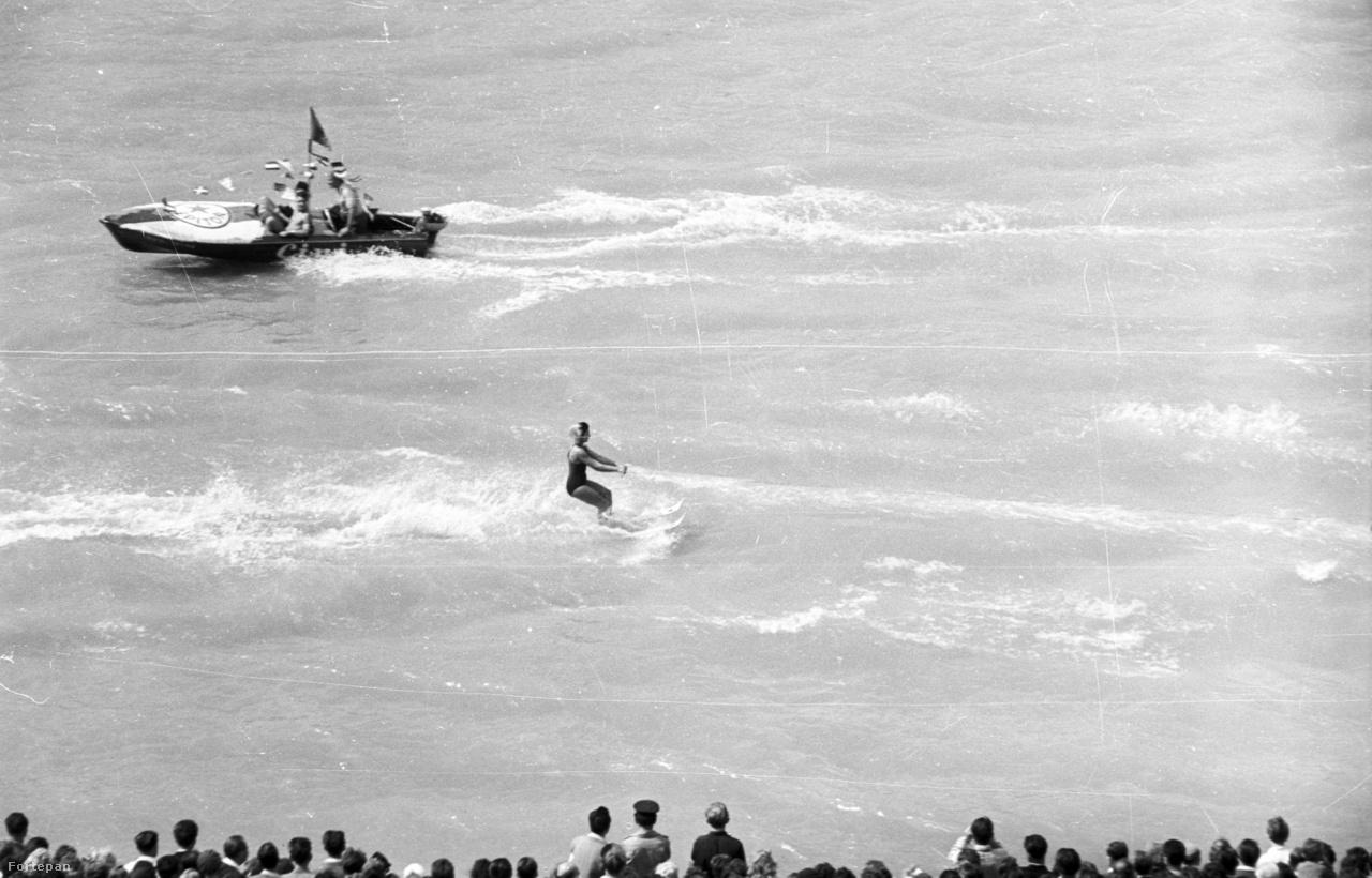 Vízisí bemutató augusztus 20-án a Széchenyi rakparttól nézve, 1960                         Már 11 éves a magyar Alkotmány! Augusztusi napsugárözönben, nagyszabású dunai vízi parádéval, kétszázezer lelkes nézővel ünnepelt a Népköztársaság.