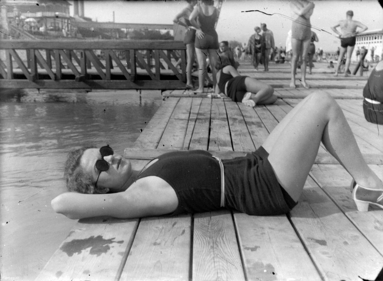 """A Budai Strandfürdő az Újlaki rakparton, a Margitszigettel szemben, 1937                         Újlakon nem volt divat a hiányos öltözet: az úszódressz kötelező volt, a napszemüveg fakultatív. A közönség """"olcsó napi árak"""" mellett élvezte a hideg és meleg vizet, a külön dunai uszodát és a standvendéglőt."""