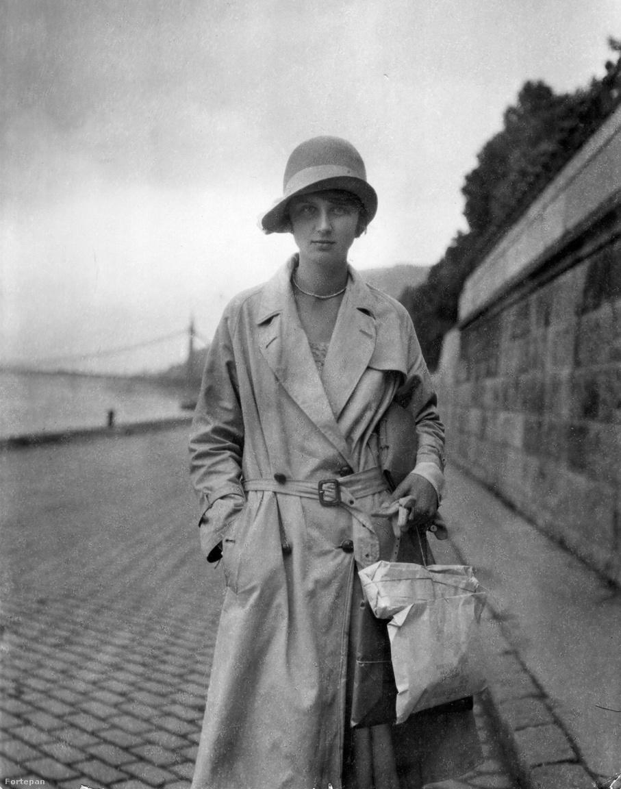 A budai alsó rakpart a mai Ybl Miklós térnél, 1926                         Decens kalap, kis gyöngysor, lazán megkötött tavaszi ballon, befelé fordított monogramos táska, kesztyű és finom papírba csomagolt, spárgával átkötött pakkok a kézben – igazi street style a keramiton! Háttérben a régi Erzsébet híd sziluettje, a kőfal felett a Várkert-rakpart fái. Ez volt a csendes budai korzó, és bár itt is volt néhány zöld bér-szék, mint a mondén pesti nagytestvérnél, a hely megmaradt a magányt kedvelőknek. Errefelé a legzajosabb esemény a környékbeli gyerekek egy-egy focimeccse volt.