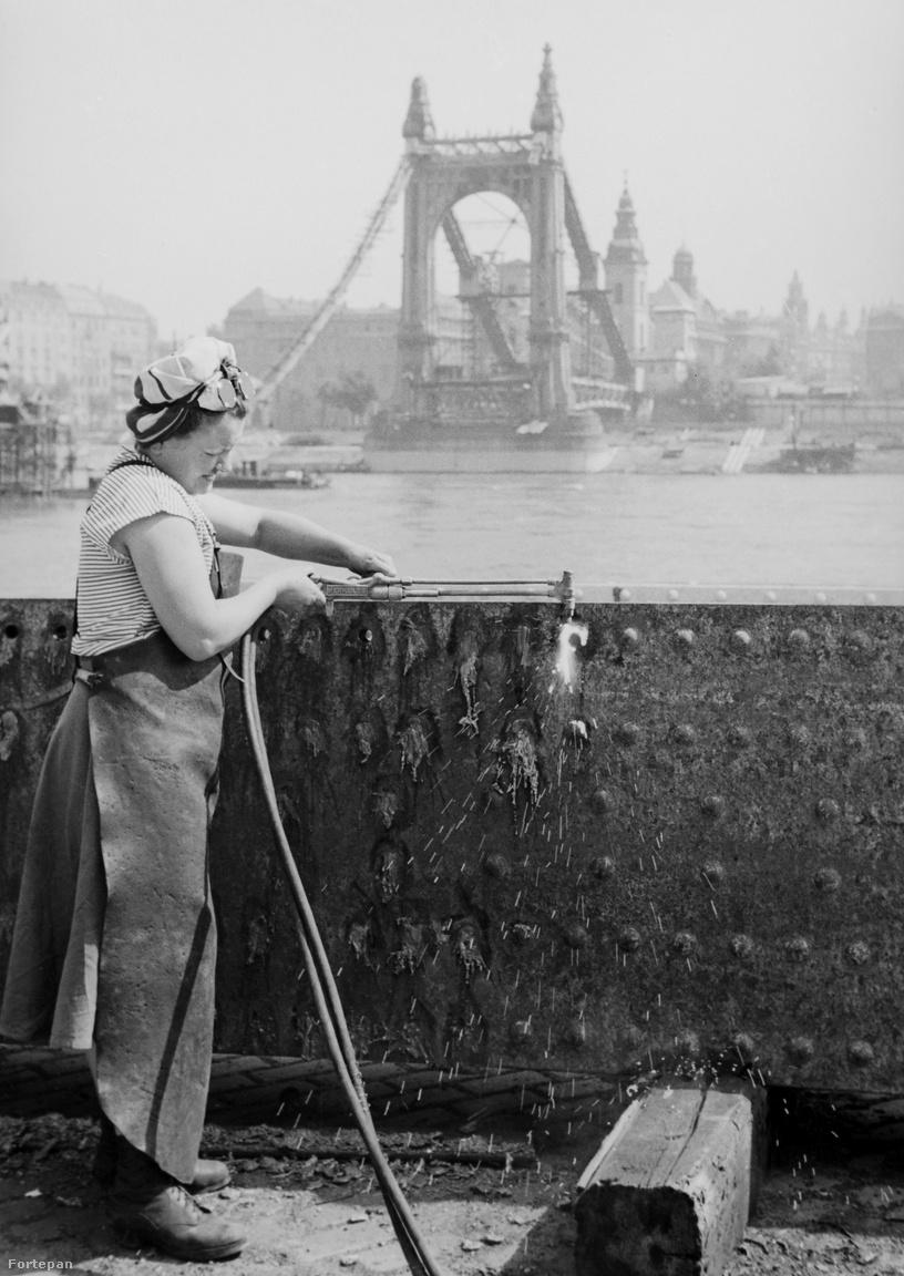 A hegesztő-lángvágó szakmunkásnő és ami az Erzsébet hídból megmaradt, 1949                         Az 1903-ban átadott híd 1945 januárjában repült a levegőbe. De, ahogy a fotón is látszik, a pesti oldalon a hídfő állva maradt és évtizedekig torzóként meredt a városra. Csak 1961-ben bontották le, amikor  hozzákezdtek a teljesen új vonalvezetésű híd építéséhez.