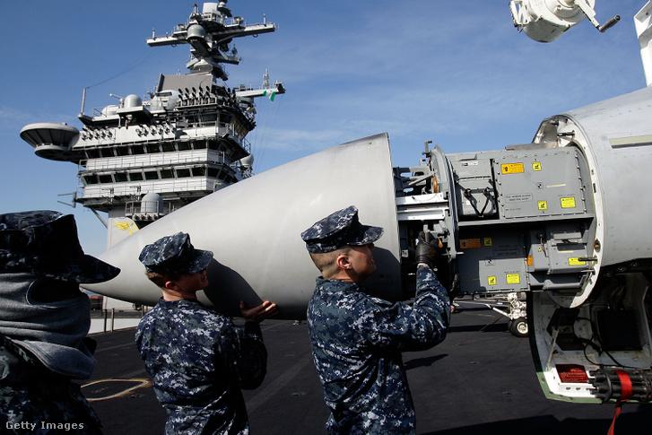 Egy F-18-as orrát szerelik amerikai katonák a USS Carl Vinson fedélzetén.