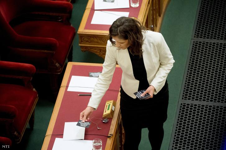 """Szél Bernadett az LMP frakcióvezetője """"külföldről finanszírozott politikus vagyok"""" feliratú cédulákat helyez el a kormány tagjainak asztalára az Országgyűlés plenáris ülésén"""