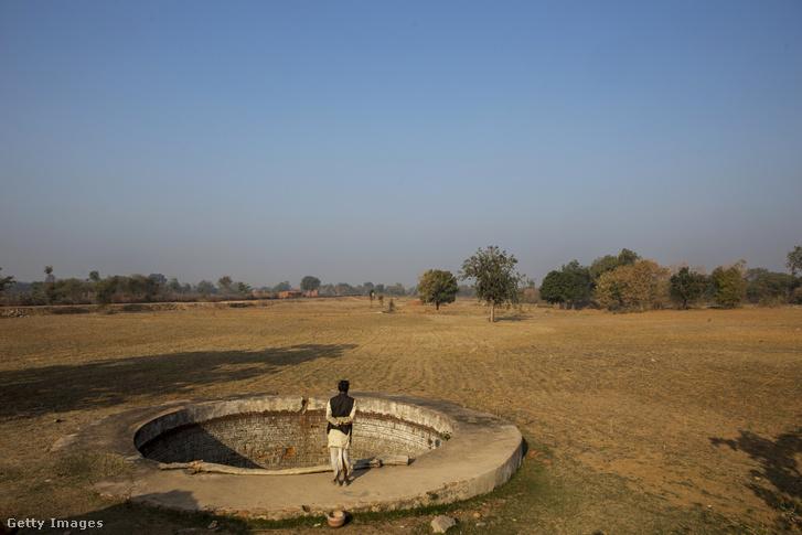 Farmer áll egy vízgyűjtő kút szélén, a kiszáradt földjén, Patharkhera falu mellett.