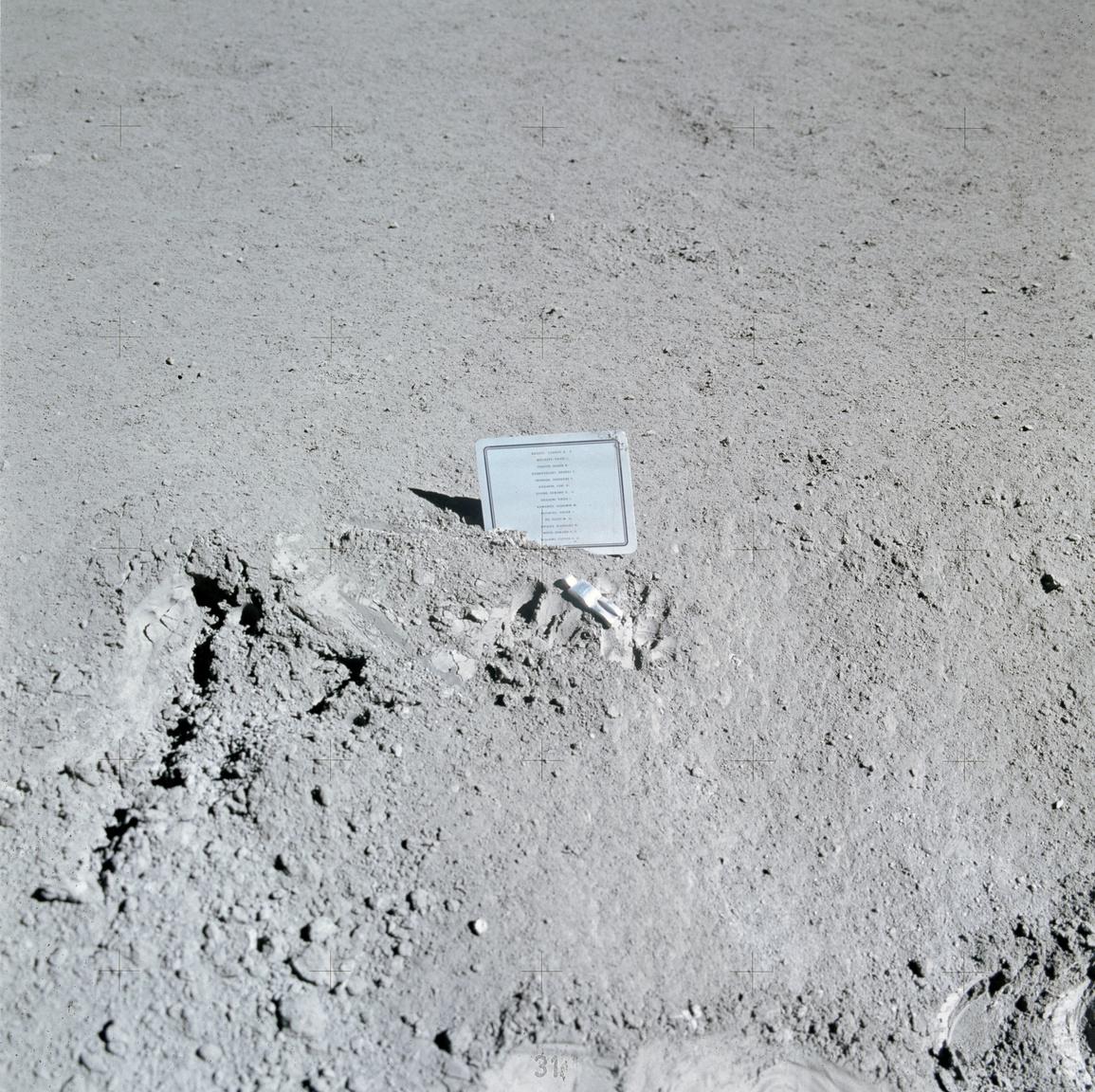 """1971. július 31 - augusztus 2. Az Apollo-15 űrhajósai, David R. Scott és James B. Irwin helyezték el a Holdon ezt az emlékplakettet, amint 14 hősi halált halt amerikai és szovjet űrhajós neve szerepel. A plakett mellett az """"Elesett űrhajós"""" szobrocskája fekszik, többek között Komarovnak is emléket állítva. (Komarovról egy krátert is elneveztek a Holdon.)"""