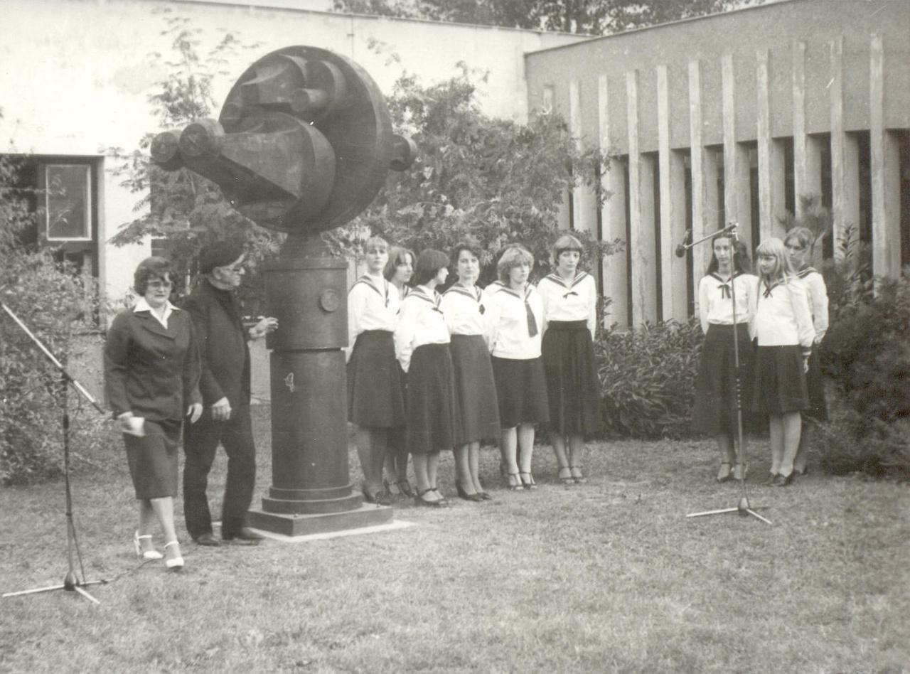 A szobor eredetileg a Komarov Gimnázium és Szakközépiskola (ma: PTE Babits M. Gyakorló Gimnázium) parkjában állt, majd felújítását követően került mai helyére a Búza térre. A kép 1979-ben, a szobor avatásán készült. A szobor bal oldalán Amerigo Tot, mellette az iskola akkori igazgatónője, Szentirányi Józsefné látható.