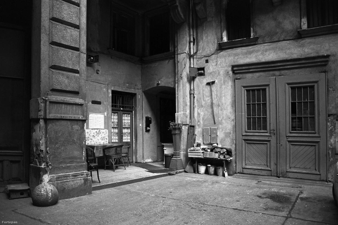 """Otthonos betonudvar a  József körút 35.-ben, 1981Ki mondta, hogy a fonott kerti székeknek, a halomba rakott tűzifának és a falra akasztott partvisnak nem lehet bája? És talán ez a bérház is megtalálja egyszer a maga Poldi nénijét-bácsiját, és egy gyors lakóközösségi gyeptéglázás után az a """"szép zöld gyep sem hiányzik"""" többé (szakirodalomként ajánljuk a pesti bérház-kertészet egyik alapművét, Janikovszky Éva Égigérő fű című könyvét)."""