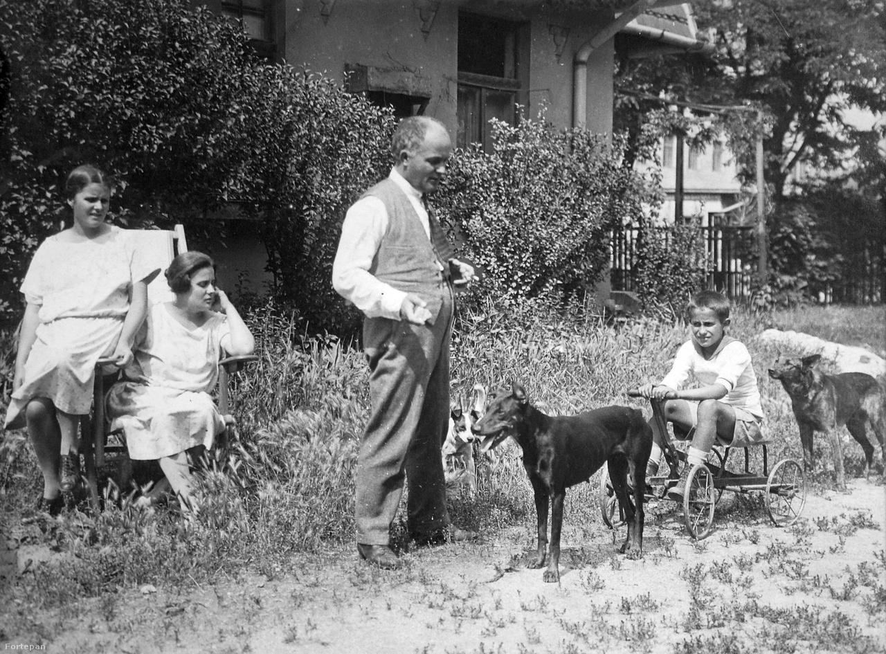 A Százados úti Művésztelep egyik kisvárosias kertje, 1925Az első lakók 1911-ben költöztek be a városszéli, kertvárosi jellegű művésztelepre, ahol nemcsak a véső és az ecset volt mindig kéznél, hanem a metszőolló is. Sőt, Czigány Dezső, Kisfaludi Stróbl Zsigmond vagy éppen a fotón szereplő Vass Viktor szobrászművész és gyermekei csirkét, libát etettek a baromfiudvaron, kecskét fejtek, kertészkedtek. A férjek a művészetekben, a feleségek a virágoskertjeik szépítésében vetélkedtek.
