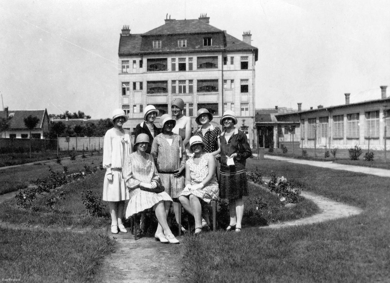 Kalap- és mosolytenger a Guttmann és Fekete harisnya-, kötszövött és kötöttárugyár munkáslakóháza előtt, 1932Az óbudai Vihar és Veder utca kereszteződésénél 1927-ben épült modern telepen az üzemcsarnok mellett állt a technikai személyzet többemeletes lakóháza. A parkosított, rózsatövekkel beültetett kertben nyolc, a némafilmkorszak eleganciáját felvonultató hölgy pillant a kamerába. A kalaporgia megpróbálja elterelni a figyelmünket a munkáslányok selyemharisnyájának diszkrét csillogásáról, de ne hagyjuk magunkat: a formás lábakat minden bizonnyal a gyárban készült, egykor világhírű GFB jelzésű selyemharisnyákba bújtatták.
