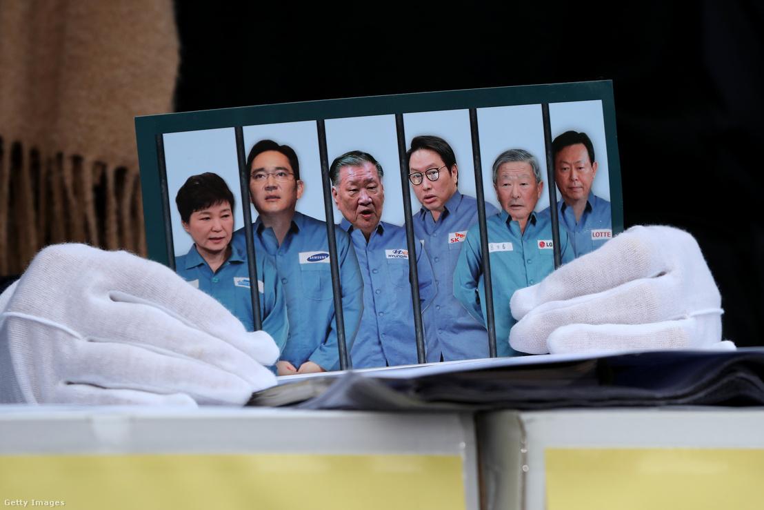 Röplap egy tüntető kezében, amin a Samsung, a Hyundai, az LG és más, koreai nagyvállalatok vezetői rabruhában állnak, egy 2017. januári tüntetésen, Szöulban.