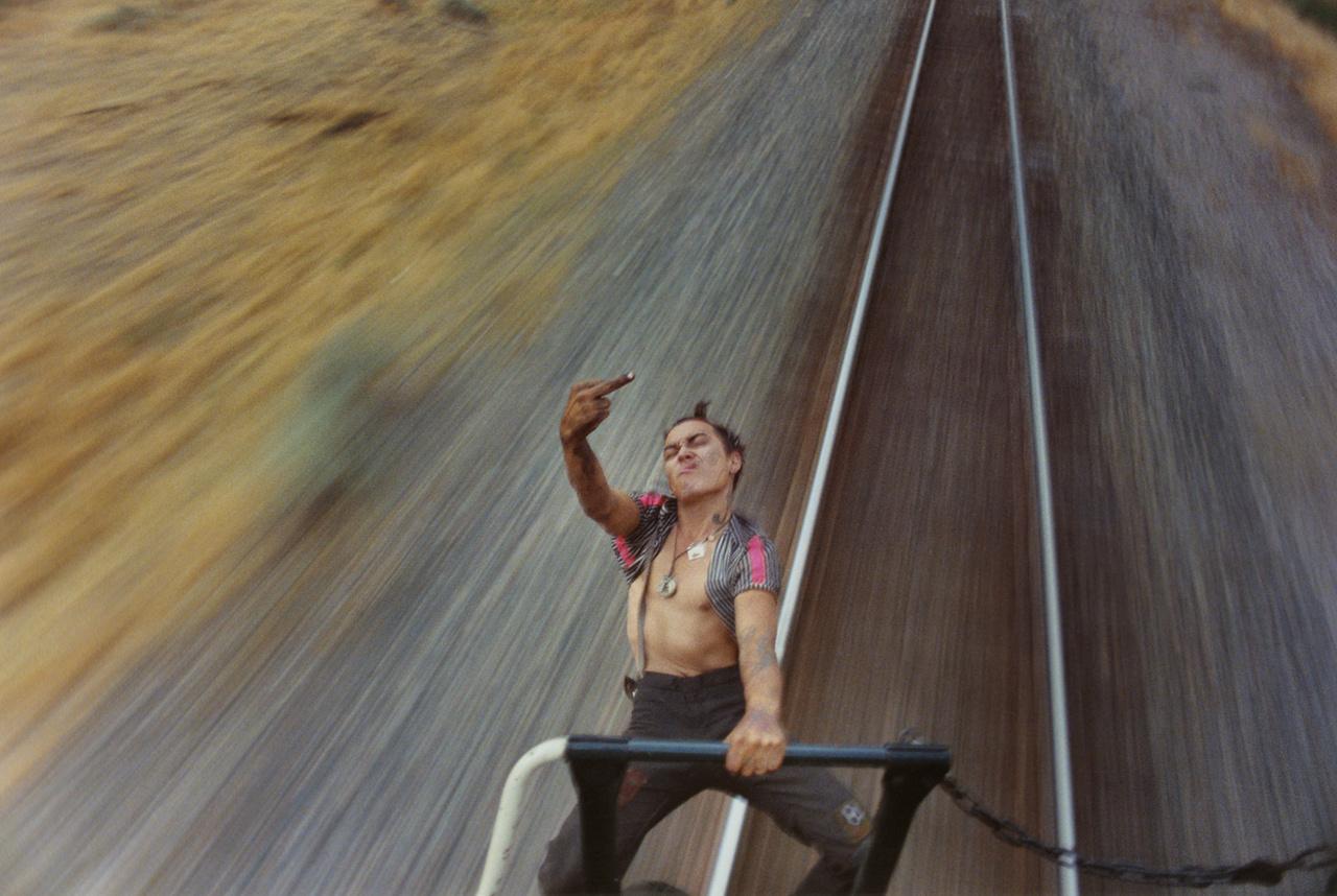 Elrobognak a jövő elől az amerikai fiatalok                         A volt BMX-es Mike Brodie eredetileg nem is akart fotós lenni, aztán szénporos csavargókról készített fotókkal került be egy befolyásos New York-i galériába, a Yossi Milóba. 18 évesen, miután egy kínai étteremben felszolgáló punk lánnyal randizva meglátott néhány csóró fiatalt, elhatározta, hogy felkapaszkodik egy vonatra, és a hagyományos amerikai értékeket a punkrock idealizmusával szembeállítva egy Polaroiddal fényképeket fog csinálni a reménytelen helyzetű, lecsúszott családokból jövő, koszos fiatalokról.
