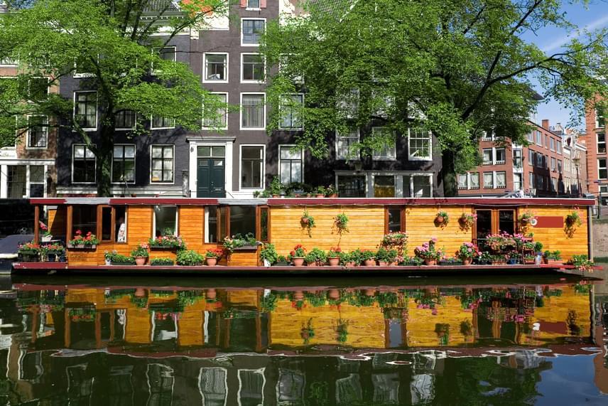 A képen látható mesebeli lakóhajó egy amszterdami csatornán horgonyoz - a hasonló otthonok szinte a város jelképeivé váltak, nem véletlen, hogy a turisták is előszeretettel szállnak meg ilyen helyeken.