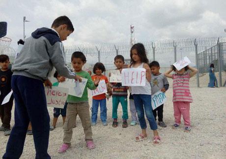 A körülmények elleni táblákat felmutató gyerekek a tompai tranzitzónában.