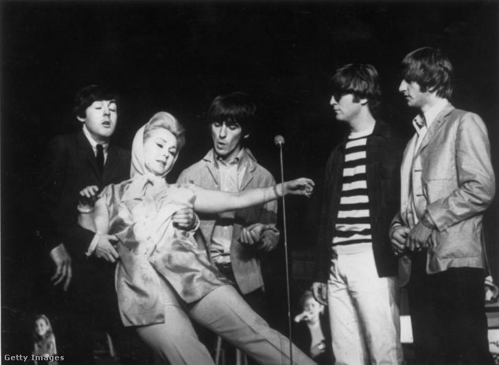 Zsazsa épp Paul McCartney karjaiba omlik a Night Of A 100 Stars jótékonysági rendezvényen a londoni Palladiumban. Mellettük a Beatles többi tagja (balról jobbra) George Harrison (1943 - 2001), John Lennon (1940 - 1980) és Ringo Starr.