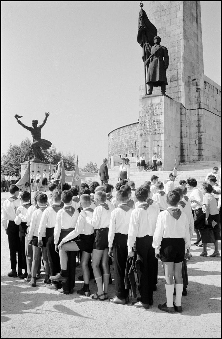 A fiatal üttörők fölé Kisfaludy Stróbl Zsigmond (1884–1975) 1947-ben felállított hatméteres felszabadító szovjet katonája emelkedik. A szobrot 1956-ban annyira megrongálták, hogy 1957-ben a szobrász újramintázta, és 1958 elején már a képen is látható helyreállított bronzszobor állt itt.