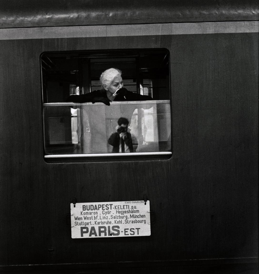 """Elliott Erwitt 1964-ben a Time magazin megbízásából járt Magyarországon. Az akkor csupán 36 éves fotográfus a megbízásra egy interjúban úgy emlékszik vissza, mint egyik legemlékezetesebb munkájára: """"Nem volt semmilyen megkötés. Szabadon fotózhattam, amit csak akartam.""""  Magyarország mellett az egykori Csehszlovákiában és Lengyelországban is fényképezett, megörökítve a szocialista országokban zajló hétköznapi élet történéseit. A Vasfüggöny keleti oldalán töltött három hónap alatt összesen 350 tekercs filmet használt fel. Ezekből a képekből jelent meg első fotóalbuma, Kelet-Európa: Csehszlovákia, Magyarország, Lengyelország (1965) címmlel. A Magyarországon töltött időszak során számos budapesti helyszínen megfordult, emellett a falusi életet is dokumentálta. Az itt készültképek közül többet is kiemel, amikor életművéről kérdezik: a Keleti pályaudvaron készült önarcképét (fent), és az induló vonat mellett búcsúzó asszonyról készült fotót.                         Erwitt megható és érzelmekkel teli szituációként írta le a Keleti pályaudvaron tapasztalt jeleneteket visszaemlékezéseiben. Úgy vélte, a vonaton ülő emberek elhagyni készültek az országot, emigrációba vonultak, és talán soha nem térhettek vissza hazájukba. A fotó(k) készítésekor igyekezett feltűnésmentes maradni, nem szerette volna, ha a rendőrség épp akkor fogja el, amikor az elbúcsúzás intim pillanatait rögzíti. """"Nagy látószögű objektívvel még egy idomított orangután is elfogadható képet csinált volna ebben a helyzetben"""" – írta."""